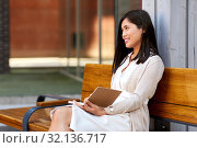 Купить «asian woman with notebook or sketchbook on bench», фото № 32136717, снято 13 июля 2019 г. (c) Syda Productions / Фотобанк Лори