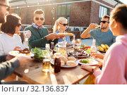 Купить «friends having dinner or bbq party on rooftop», фото № 32136837, снято 2 сентября 2018 г. (c) Syda Productions / Фотобанк Лори