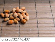 Купить «Hazelnut fruits. Healthy diet vegetarian food. Filbert natural healthy hazel sprinkled on a brown background. Crop Production, Nut Harvesting Season», фото № 32140437, снято 1 сентября 2019 г. (c) Светлана Евграфова / Фотобанк Лори
