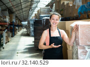 Купить «Female in apron standing near shelves with cardboard boxes for packaging», фото № 32140529, снято 15 сентября 2019 г. (c) Яков Филимонов / Фотобанк Лори