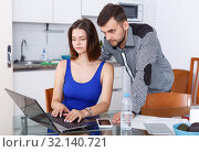 Young woman looking at laptop and man standing at home. Стоковое фото, фотограф Яков Филимонов / Фотобанк Лори