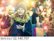 Купить «Young woman delighted with Christmas toys at fair», фото № 32140797, снято 14 декабря 2017 г. (c) Яков Филимонов / Фотобанк Лори