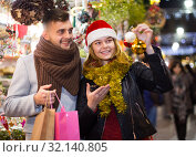 Купить «young couple in Christmas hat buying decoration at fair», фото № 32140805, снято 14 декабря 2017 г. (c) Яков Филимонов / Фотобанк Лори
