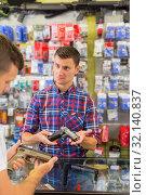 Купить «Salesman helping customer to choice air gun», фото № 32140837, снято 4 июля 2017 г. (c) Яков Филимонов / Фотобанк Лори