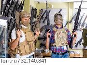 Купить «Male customers try on ammunition with weapon», фото № 32140841, снято 4 июля 2017 г. (c) Яков Филимонов / Фотобанк Лори