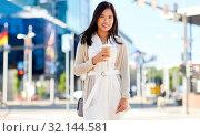 Купить «smiling woman with takeaway coffee cup in city», фото № 32144581, снято 13 июля 2019 г. (c) Syda Productions / Фотобанк Лори