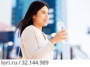 Купить «asian woman drinking water from bottle in city», фото № 32144989, снято 13 июля 2019 г. (c) Syda Productions / Фотобанк Лори
