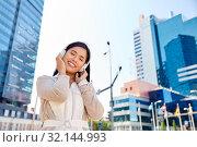 Купить «happy smiling asian woman with headphones in city», фото № 32144993, снято 13 июля 2019 г. (c) Syda Productions / Фотобанк Лори