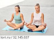 Купить «women doing yoga and meditating in lotus pose», фото № 32145037, снято 28 июля 2019 г. (c) Syda Productions / Фотобанк Лори
