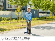 Купить «happy little boy riding scooter in city», фото № 32145069, снято 1 августа 2019 г. (c) Syda Productions / Фотобанк Лори