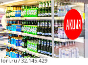 Купить «Beer cans and bottles in supermarket. Text in Russian: Action (Sale)», фото № 32145429, снято 30 марта 2019 г. (c) FotograFF / Фотобанк Лори