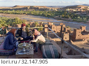 People sitting on the terrace of a cafe overlooking the Ksar of Ait-Ben-Haddou, Ounila River valley, Ouarzazate Province, region of Draa-Tafilalet, Morocco, North West Africa. (2019 год). Редакционное фото, фотограф Christian Goupi / age Fotostock / Фотобанк Лори