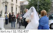 Купить «Father throws a veil over the face of beautiful daughter. Bride coming to church», видеоролик № 32152437, снято 18 мая 2019 г. (c) Ирина Мойсеева / Фотобанк Лори