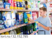 Купить «Serious tweenager boy choosing household chemicals in shop», фото № 32152785, снято 4 июня 2018 г. (c) Яков Филимонов / Фотобанк Лори
