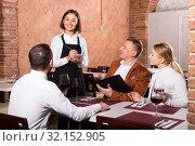 polite woman waiter receiving order from guests in restaurant. Стоковое фото, фотограф Яков Филимонов / Фотобанк Лори