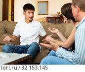 Angry parents quarrelling with his upset teenage son at home. Стоковое фото, фотограф Яков Филимонов / Фотобанк Лори
