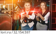 Купить «Portrait of two women in business suits playing laser tag with c», фото № 32154597, снято 4 апреля 2019 г. (c) Яков Филимонов / Фотобанк Лори