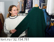Купить «Woman choosing new overcoat in store», фото № 32154781, снято 6 декабря 2018 г. (c) Яков Филимонов / Фотобанк Лори