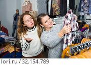 Купить «Women choosing new overcoat», фото № 32154789, снято 6 декабря 2018 г. (c) Яков Филимонов / Фотобанк Лори