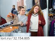 Купить «Woman trying new overcoat», фото № 32154805, снято 6 декабря 2018 г. (c) Яков Филимонов / Фотобанк Лори