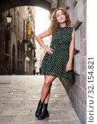 Купить «Cheerful young girl standing near brick wall at street in Barcelona», фото № 32154821, снято 24 сентября 2018 г. (c) Яков Филимонов / Фотобанк Лори
