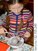 Семилетняя девочка посыпает елочную игрушку блестками. Детский мастер-класс в мастерской (2018 год). Редакционное фото, фотограф Ирина Борсученко / Фотобанк Лори