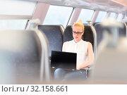 Купить «Businesswoman sitting and traveling by train working on laptop. Business travel concept.», фото № 32158661, снято 16 февраля 2020 г. (c) easy Fotostock / Фотобанк Лори