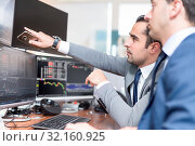 Купить «Businessmen trading stocks online. Stock brokers looking at graphs, indexes and numbers on multiple computer screens. Colleagues in discussion in traders office. Business success concept.», фото № 32160925, снято 9 июля 2020 г. (c) easy Fotostock / Фотобанк Лори