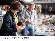 Positive elderly woman choosing interesting souvenirs at flea market. Стоковое фото, фотограф Яков Филимонов / Фотобанк Лори