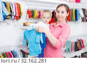 Купить «Positive woman choosing clothes with little son», фото № 32162281, снято 18 апреля 2018 г. (c) Яков Филимонов / Фотобанк Лори