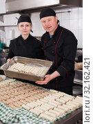 Купить «Two cooks holding baking tray with cannelloni», фото № 32162421, снято 11 апреля 2019 г. (c) Яков Филимонов / Фотобанк Лори