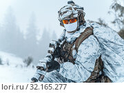 Купить «Winter arctic mountains warfare. Action in cold conditions. Trooper with weapons in forest somewhere above the Arctic Circle.», фото № 32165277, снято 25 мая 2020 г. (c) easy Fotostock / Фотобанк Лори