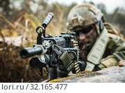 Купить «Norwegian Rapid reaction special forces FSK soldier firing in the forest. Field camo uniforms, combat helmet and eye-wear goggles are on.», фото № 32165477, снято 25 мая 2020 г. (c) easy Fotostock / Фотобанк Лори