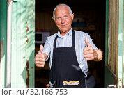 Купить «Happy man in doorway of garden shed», фото № 32166753, снято 13 июня 2018 г. (c) Яков Филимонов / Фотобанк Лори