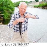 Купить «Adult fisherman removing catch from hook», фото № 32166797, снято 10 июня 2018 г. (c) Яков Филимонов / Фотобанк Лори