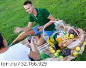 Купить «Man enjoying life on picnic outdoors with his friend», фото № 32166929, снято 23 августа 2017 г. (c) Яков Филимонов / Фотобанк Лори
