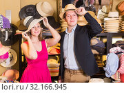 Купить «Smiling woman and man trying on fashion hats», фото № 32166945, снято 2 мая 2017 г. (c) Яков Филимонов / Фотобанк Лори