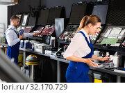 Купить «Smiling female car painter preparing paints for paintwork in modern auto repair shop», фото № 32170729, снято 4 апреля 2018 г. (c) Яков Филимонов / Фотобанк Лори