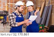 Купить «Disgruntled foreman discussing drawing with worker», фото № 32170861, снято 6 марта 2019 г. (c) Яков Филимонов / Фотобанк Лори
