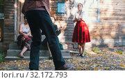 A woman playing the balalaika and a man dancing folklore dancing near the country house. Стоковое видео, видеограф Константин Шишкин / Фотобанк Лори