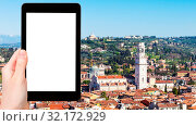 Travel concept - tourist photographs above view of Verona city with Duomo Cathedral from tower Torre dei Lamberti in spring on tablet with cut out screen for advertising logo. Стоковое фото, фотограф Zoonar.com/Valery Voennyy / easy Fotostock / Фотобанк Лори