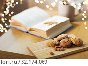 oat cookies, almonds and book on table at home. Стоковое фото, фотограф Syda Productions / Фотобанк Лори