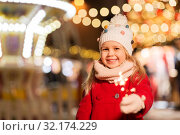 Купить «happy girl with sparkler at christmas market», фото № 32174229, снято 4 января 2019 г. (c) Syda Productions / Фотобанк Лори