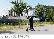 Купить «young businessman riding electric scooter outdoors», фото № 32174345, снято 1 августа 2019 г. (c) Syda Productions / Фотобанк Лори