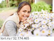 Купить «happy woman smelling chamomile flowers in garden», фото № 32174465, снято 12 июля 2019 г. (c) Syda Productions / Фотобанк Лори