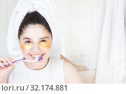 Купить «Girl in gold patches wirth teeth brush in bathroom in morning», фото № 32174881, снято 6 июля 2019 г. (c) Papoyan Irina / Фотобанк Лори
