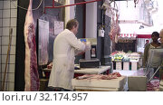 A butchershop. Meat carcasses hunged on hooks. butcher chopping meat, wrapping it in paper (2019 год). Редакционное видео, видеограф Ирина Мойсеева / Фотобанк Лори