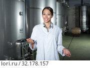 Купить «Young woman in uniform standing in winery fermentation», фото № 32178157, снято 13 декабря 2019 г. (c) Яков Филимонов / Фотобанк Лори