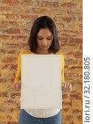 Купить «Blank canvas held in front of brick wall», фото № 32180805, снято 23 июля 2019 г. (c) Wavebreak Media / Фотобанк Лори