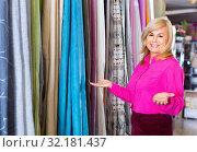 Купить «Positive mature woman seller showing curtain in the curtains shop», фото № 32181437, снято 17 января 2018 г. (c) Яков Филимонов / Фотобанк Лори